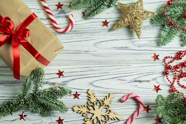 Decorazioni del fondo della struttura di natale con i rami, il presente, il bastoncino di zucchero, i fiocchi di neve e la stella di abete Foto Premium