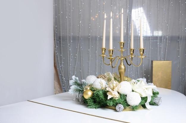 Decorazioni di capodanno e un candelabro d'oro con candele accese stanno sulla superficie di un pianoforte a coda bianco Foto Premium