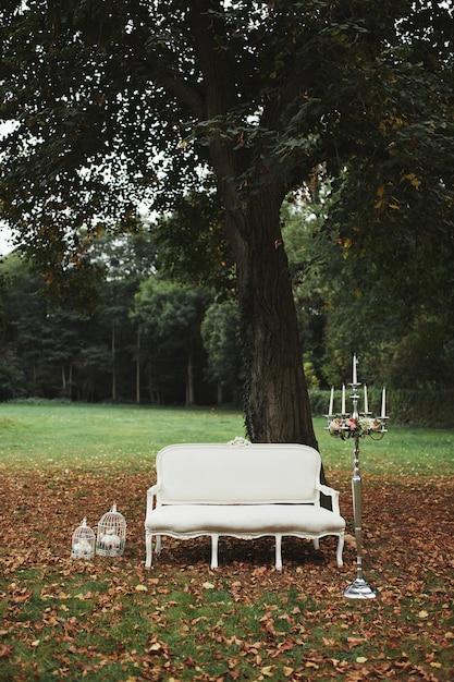 Decorazioni di nozze per servizio fotografico. divano classico bianco nella natura. candelabro nell'interno Foto Premium
