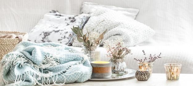 Decorazioni domestiche all'interno. coperta turchese e cestino di vimini con un vaso di fiori e candele Foto Premium