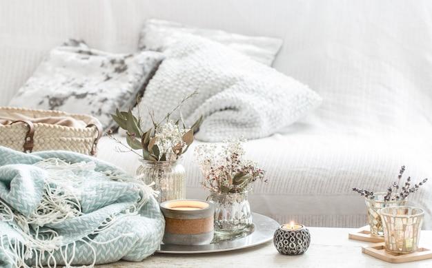 Decorazioni domestiche all'interno. coperta turchese e cestino di vimini con un vaso di fiori e candele Foto Gratuite