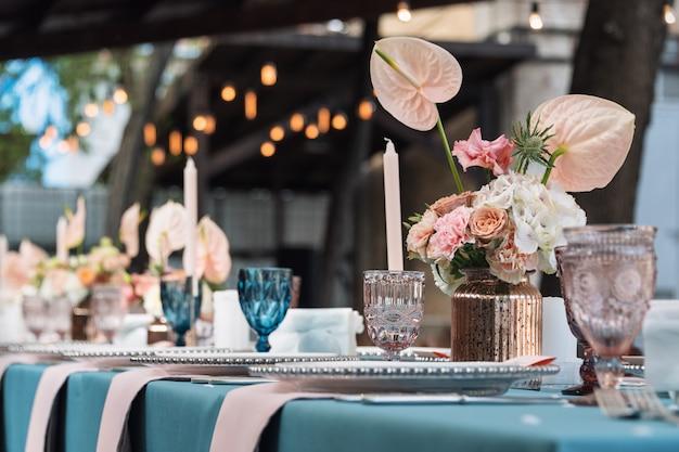 Decorazioni floreali da tavola per feste e cene nuziali. tavolo apparecchiato per il ricevimento di nozze nel ristorante all'aperto. Foto Premium