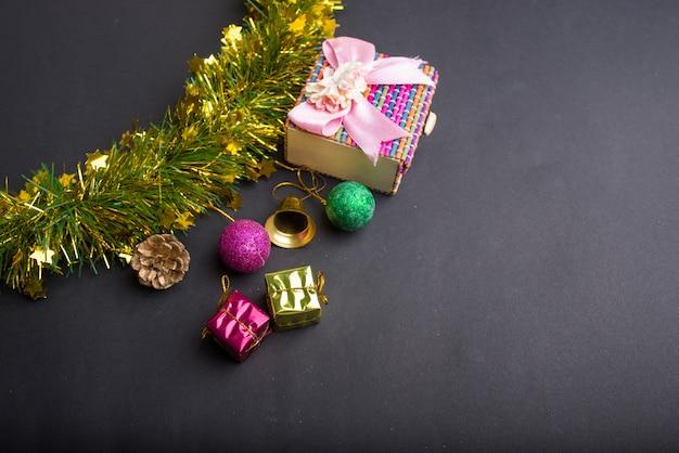 Decorazioni natalizie con sfondo nero scuro. vista dall'alto, copia spazio. palla, confezione regalo, babbo natale, nastro, ramo di pino, campana. Foto Premium