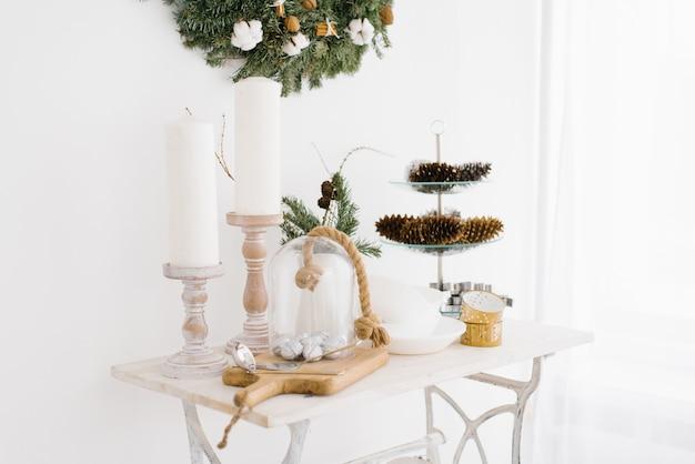 Decorazioni natalizie e di capodanno sul tavolino del salotto in casa. candele e coni Foto Premium