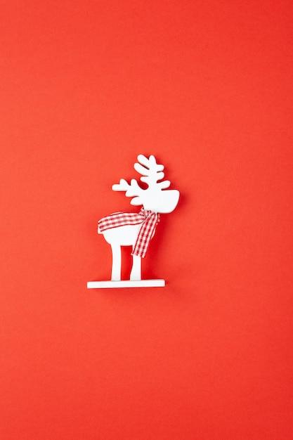 Decorazioni natalizie, giocattolo cervo bianco in sciarpa a scacchi su sfondo rosso Foto Premium