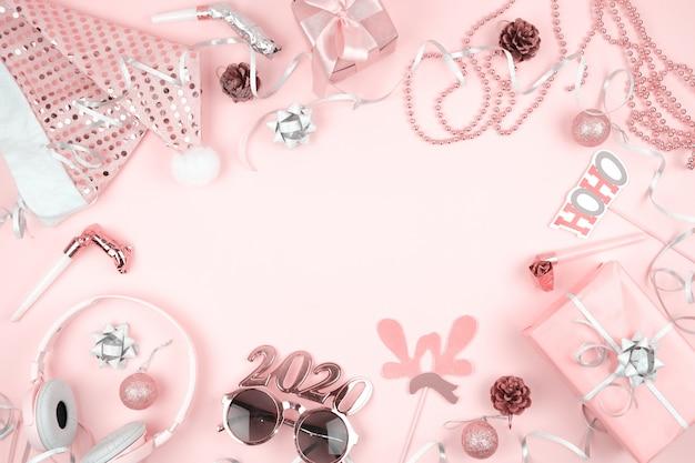 Decorazioni natalizie rosa pastello per la cornice di san silvestro, su sfondo rosa Foto Premium