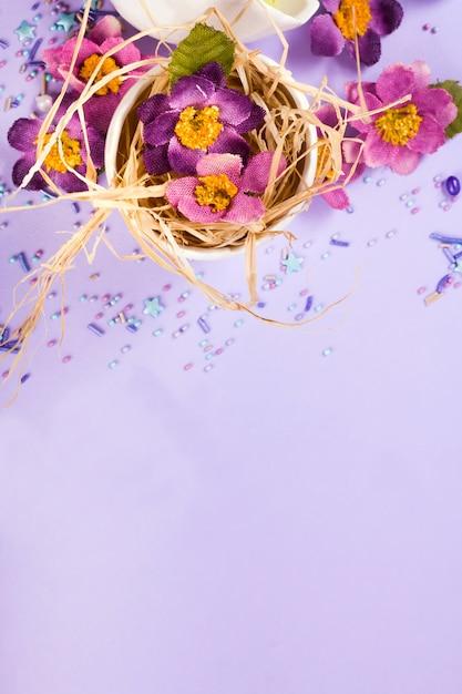 Decorazioni pasquali in colori pastello. uova di pasqua, caramelle, dolci, fiori e gusci d'uovo. Foto Premium