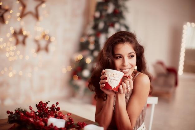 Decorazioni per le vacanze invernali colori caldi. affascinante donna bruna in abito beige Foto Gratuite