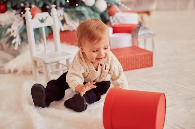 Decorazioni per le vacanze invernali colori caldi. la bella bambina gioca con le scatole attuali Foto Gratuite