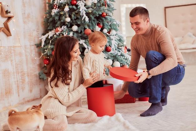 Decorazioni per le vacanze invernali colori caldi. mamma, papà e piccola figlia giocano con un cane Foto Gratuite