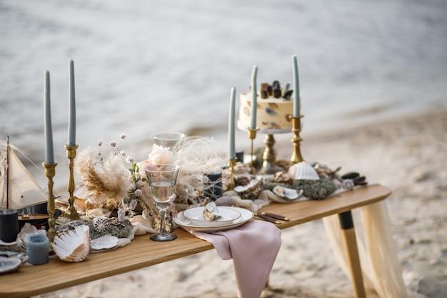 Decorazioni per matrimoni in mare sulla costa. torta nuziale e fiori all'evento. Foto Premium