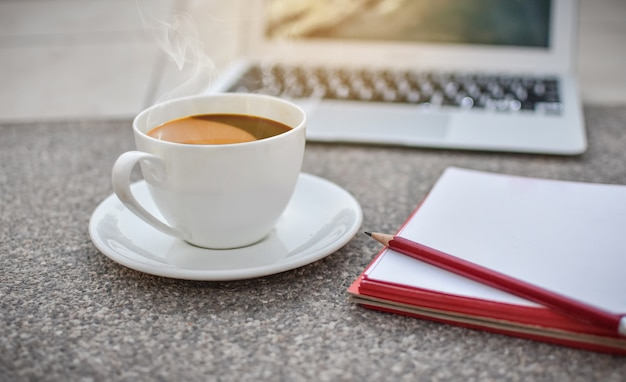 Defocus tazza di caffè a terra con notebook e laptop, mattina, caffè caldo Foto Premium