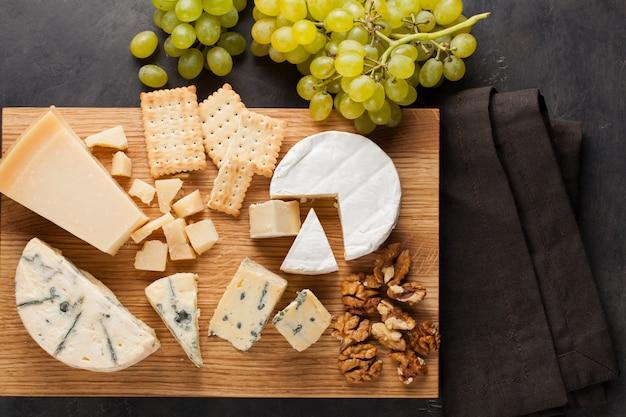 Degustazione piatto di formaggio su un piatto di legno. Foto Premium