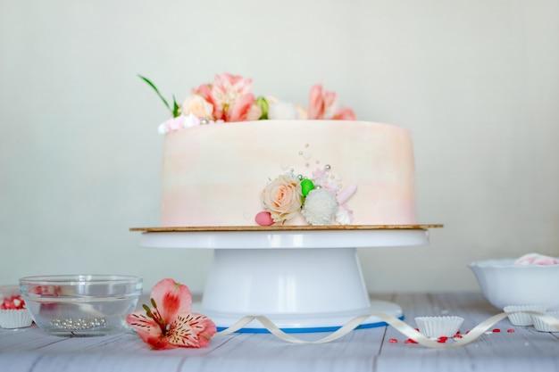 Delicata torta nuziale rosa con bellissimi fiori freschi naturali Foto Premium