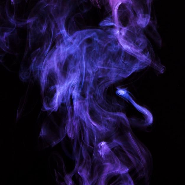 Delicato movimento di fumo di sigaretta viola su sfondo nero Foto Gratuite