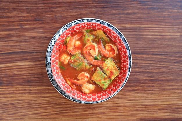 Delicious giallo curry giallo con gamberetti e frittata di verdure erba fritta in ciotola Foto Premium