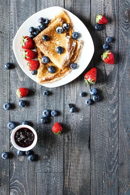 Deliziosa colazione a base di crepes con legno chiaro drammatico Foto Premium