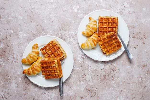 Deliziosa colazione con caffè, succo d'arancia, waffle, cornetti, marmellata, pasta di noci alla luce, vista dall'alto Foto Gratuite