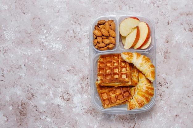 Deliziosa colazione con mandorle, fette di mele rosse, waffle, cornetti su scatola di plastica per il pranzo alla luce Foto Gratuite