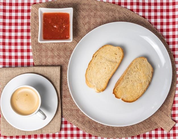 Deliziosa colazione mediterranea composta da toast con pomodoro e caffè, servita su una tovaglia scozzese vintage e un tovagliolo di tela. . Foto Premium
