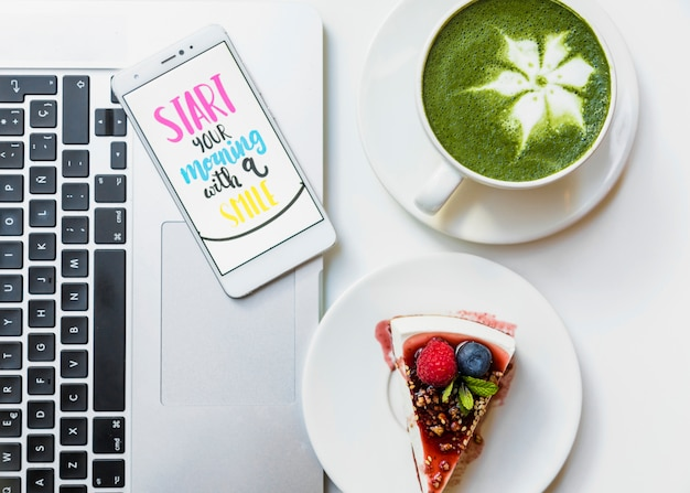 Deliziosa fetta di torta; tazza di tè matcha e cellulare con messaggio sul portatile sopra il tavolo Foto Gratuite