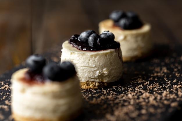 Deliziosa mini cheesecake fatta a mano con superficie in legno rustico Foto Premium