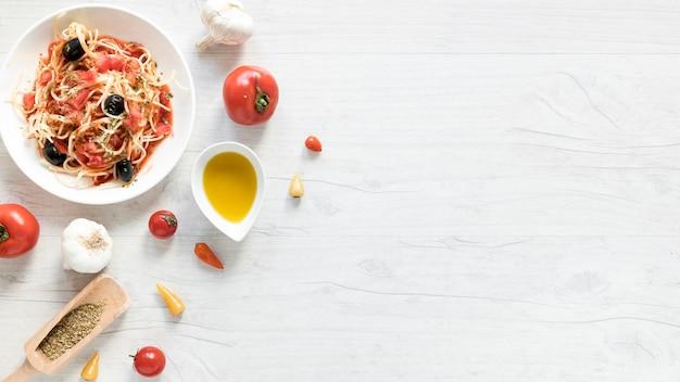 Deliziosa pasta spaghetti sul piatto; pomodoro fresco; ciotola di olio d'oliva ed erbe sulla scrivania in legno Foto Gratuite