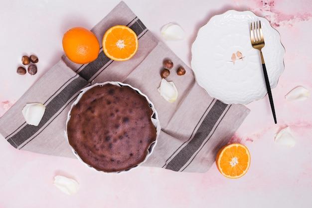 Deliziosa torta al forno; nocciola; agrumi e petali bianchi su sfondo con texture Foto Gratuite