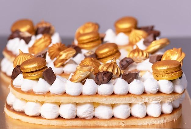 Deliziosa torta alla crema decorata con dolci dorati. Foto Premium