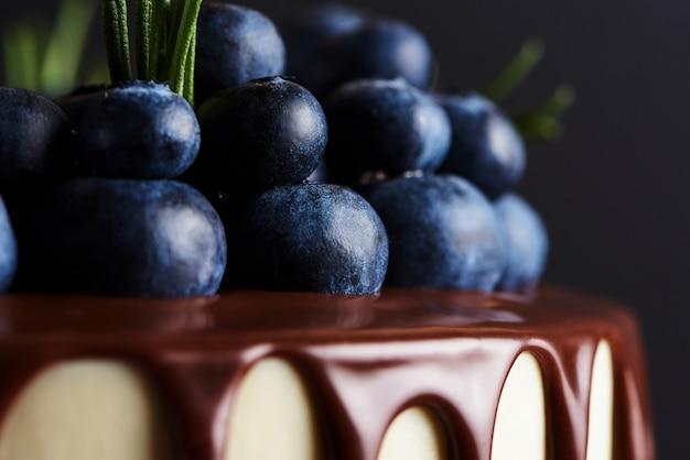 Deliziosa torta fatta in casa decorata con mirtilli freschi su un supporto in legno bianco. sfondo scuro macro. Foto Premium