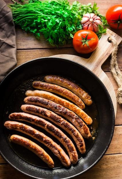 Deliziose salsicce fritte con crosta dorata in padella di ferro, pomodori freschi prezzemolo sul tavolo di legno Foto Premium