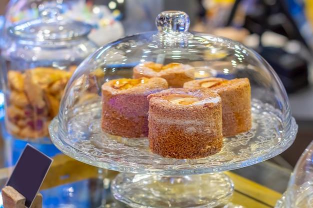 Deliziose torte in una torta di vetro stand sul bancone del bar. buffet di dolci, conservazione Foto Premium