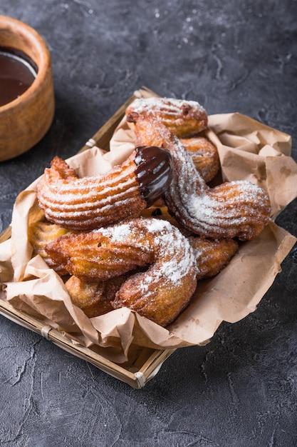 Deliziosi churros in padella fritti e spolverati con zucchero a velo Foto Premium