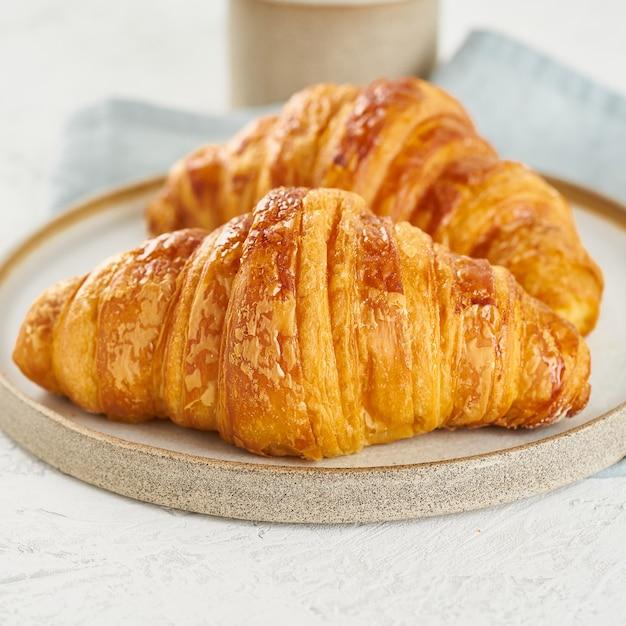 Deliziosi cornetti sul piatto e bevanda calda in tazza. mattina colazione francese con dolci freschi Foto Premium