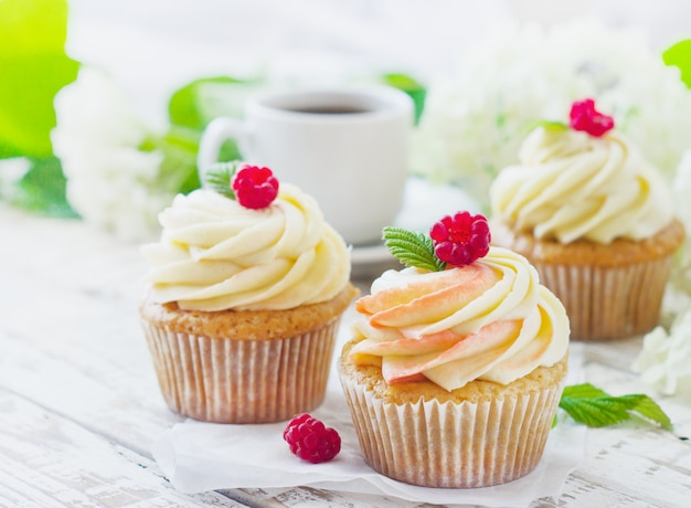 Deliziosi cupcakes alla vaniglia con panna e lamponi su legno bianco Foto Premium