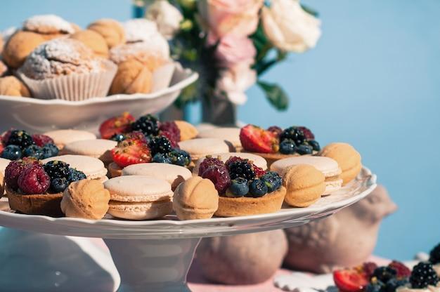 Delizioso buffet dolce con cupcakes, amaretti, altri dessert, design blu Foto Premium