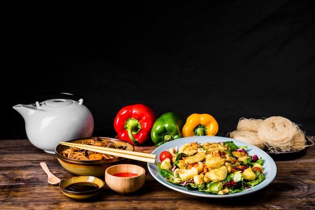 Delizioso cibo tailandese con salsa di soia; teiera e peperoni su scrivania su sfondo nero Foto Gratuite