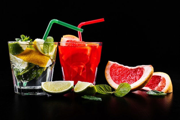 Delizioso mojito, rum e cola, arancia rossa e cocktail di vodka serviti con frutta Foto Gratuite