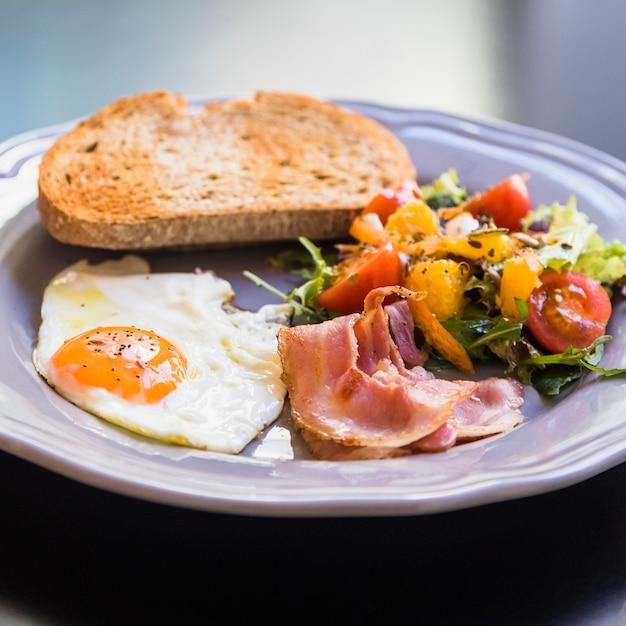 Delizioso toast; uovo mezzo fritto; pancetta e insalata sul piatto grigio Foto Gratuite