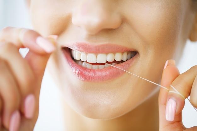 Denti bianchi sani di filo interdentale sorridenti della bella donna. Foto Premium