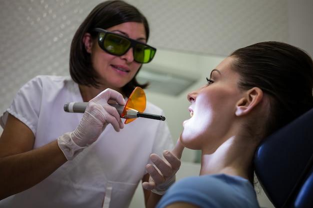 Denti d'esame dei pazienti del dentista con luce di cura dentale Foto Gratuite