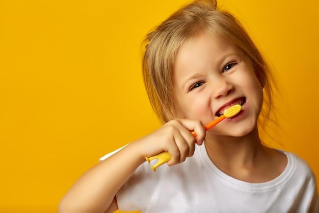 Denti di spazzolatura della ragazza adorabile con lo spazzolino da denti dei bambini Foto Premium