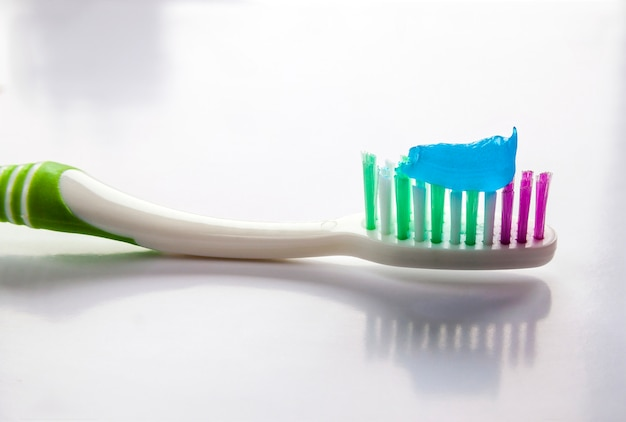 Dentifricio su un primo piano spazzolino da denti su uno sfondo di luce bianca Foto Premium