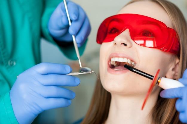 Dentista che esamina i denti di un paziente nella clinica dentale. Foto Premium