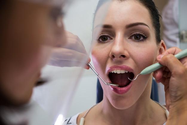 Dentista che esamina un paziente femminile con gli strumenti Foto Gratuite