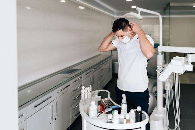 Dentista che indossa maschera chirurgica in ufficio Foto Gratuite