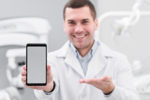 Dentista che presenta smartphone Foto Gratuite