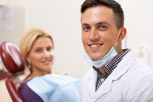 Dentista maschio bello che sorride alla macchina fotografica, il suo paziente femminile felice sui precedenti. Foto Premium