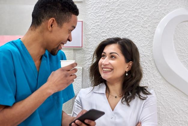 Dentisti africani e caucasici in pausa caffè Foto Premium