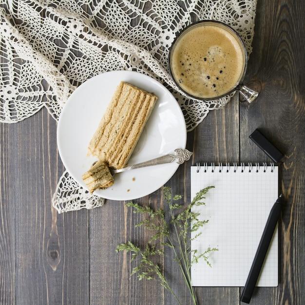 Derida l'area di lavoro con erba selvatica, penna, taccuino, fetta di torta e tazza di caffè su fondo di legno. vista piana, vista dall'alto. concetto femminile elegante Foto Premium